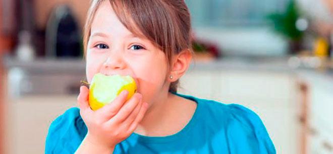 Девочка ест яблоко
